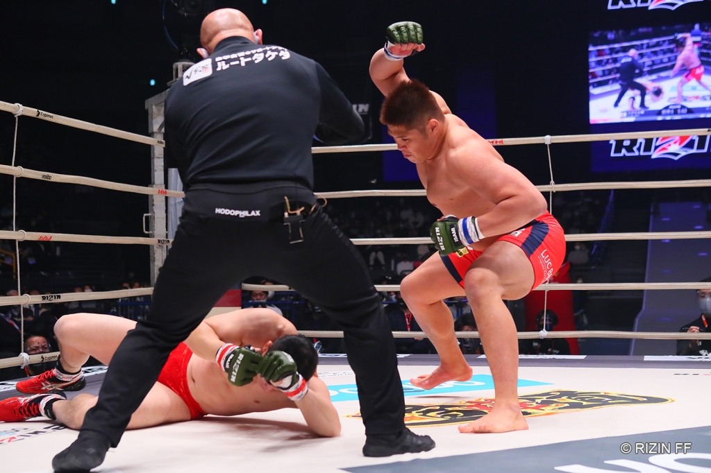 Tsuyoshi Sudario lands a hammerfist punch after dropping Minowaman with leg kicks (© RIZIN FF)
