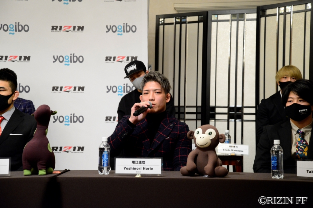 Yoshinori Horie speaks into a microphone at a RIZIN press conference.