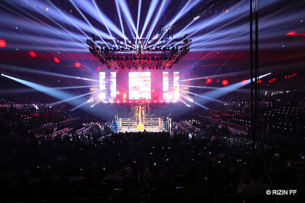 A wide shot of the Saitama Super Arena in Saitama, Japan, which has a lit stage and lights around.