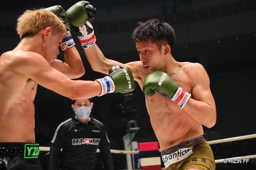 Ryota Naito charges forward at HIROKI with punches