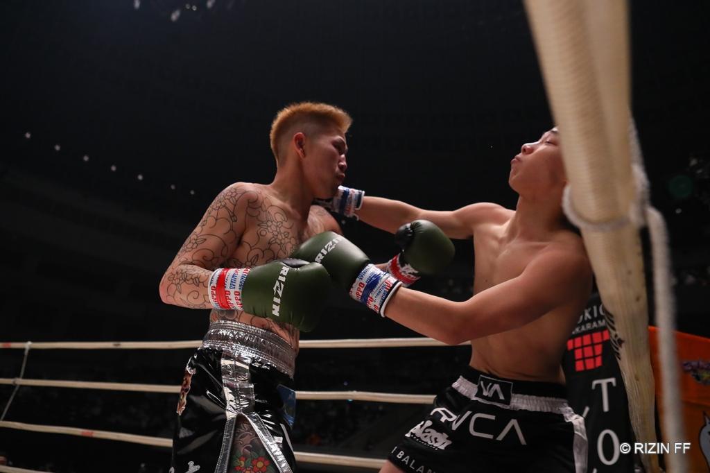 Riki Sakurai snaps Riku Yoshida back with punches against the ropes