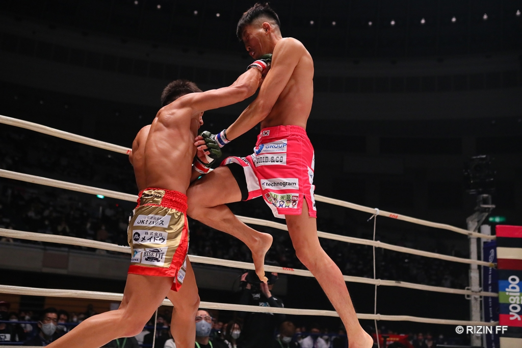 Yutaro Muramoto lands a right hook while Seigo Yamamoto comes forward with a flying knee
