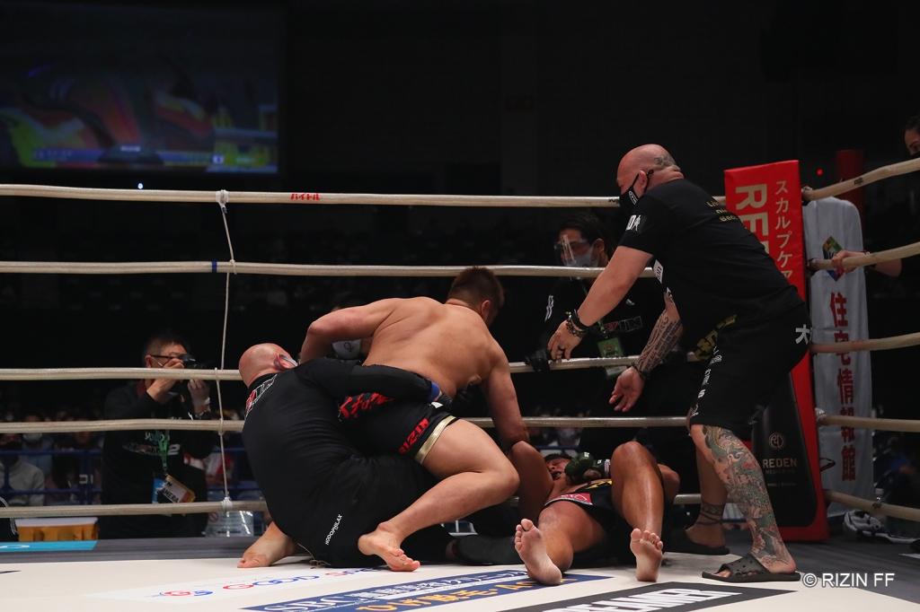Tsuyoshi Sudario lands a punch on Kazushi Miyamoto while the referee attempts to pull him off.