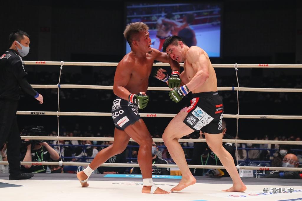 Koji Takeda throws a left hook at Takasuke Kume