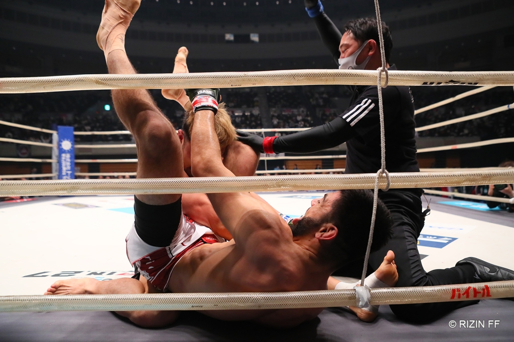 The referee instructs Roberto Satoshi Souza to let go of his triangle choke after Kazuki Tokudome tapped out