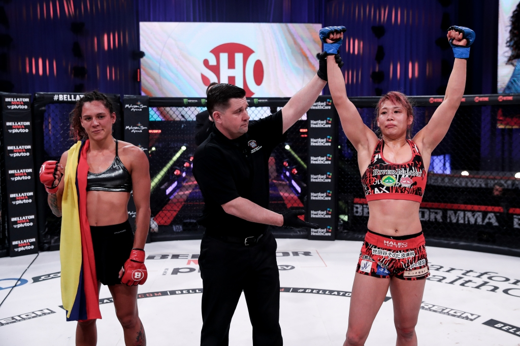 Kana Watanabe gets her arm raised by the referee. Alejandra Lara stands on the other side of the referee.