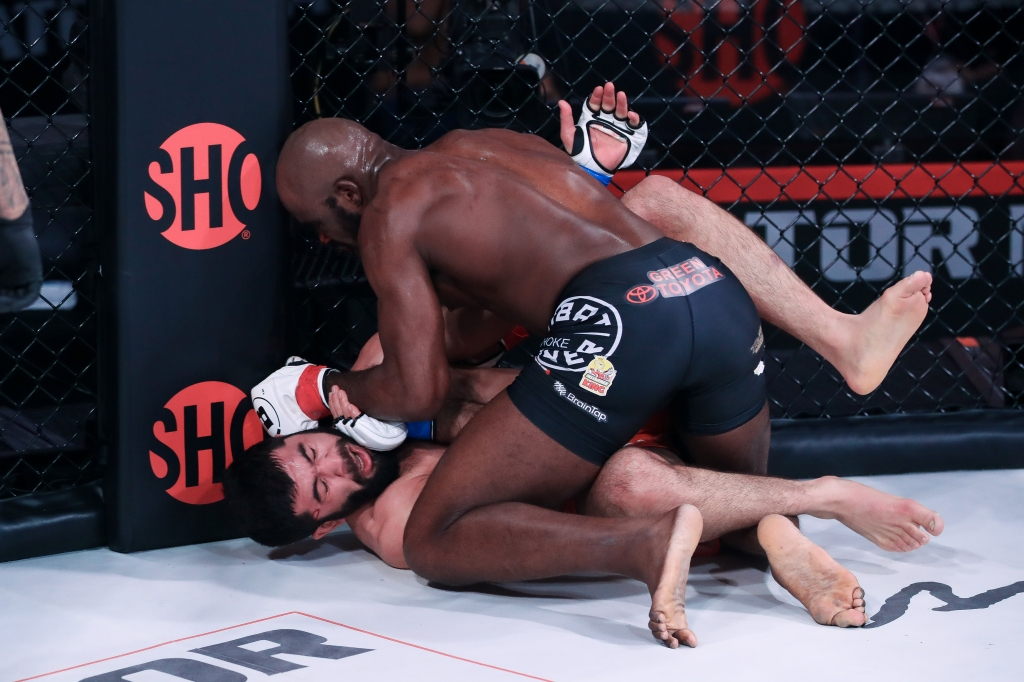 Corey Anderson throws down a left hand to the head of Dovletdzhan Yagshimuradov while on top in half guard.