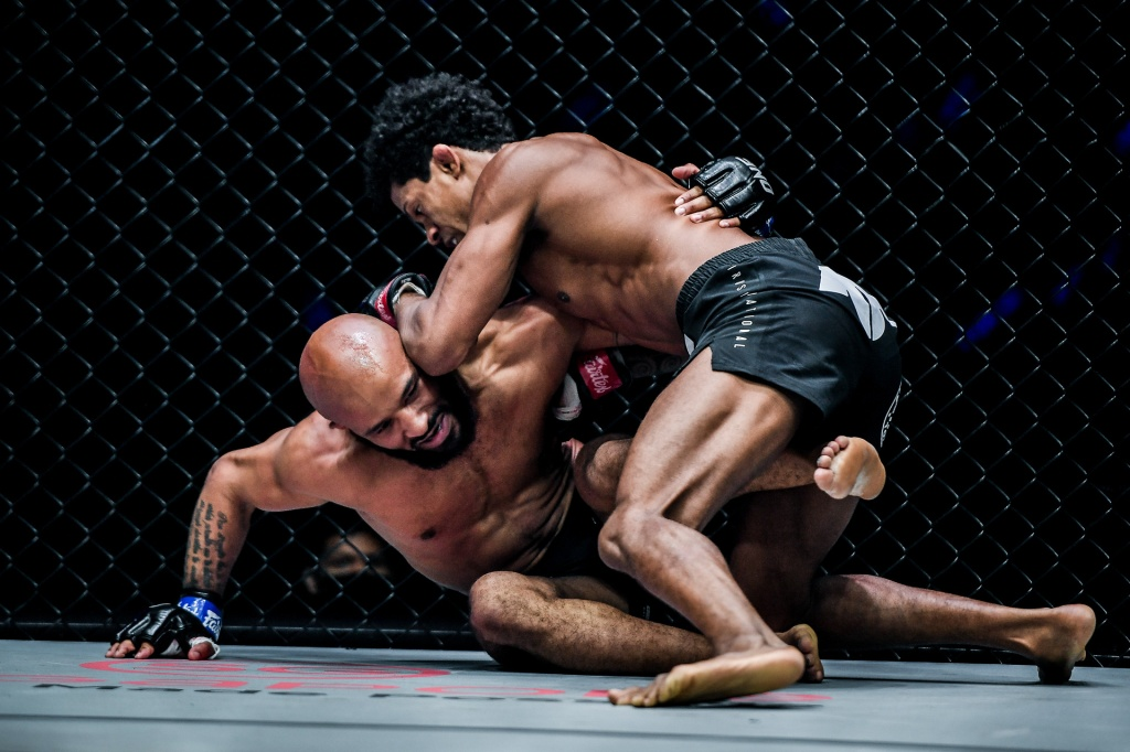 Adriano Moraes holds the head of a grounded Demetrious Johnson before landing a fight-ending knee.