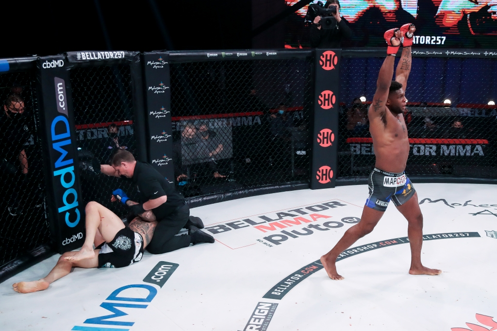 Paul Daley walks away with his arms up after defeating Sabah Homasi, who is on the ground and being attended to by a referee.