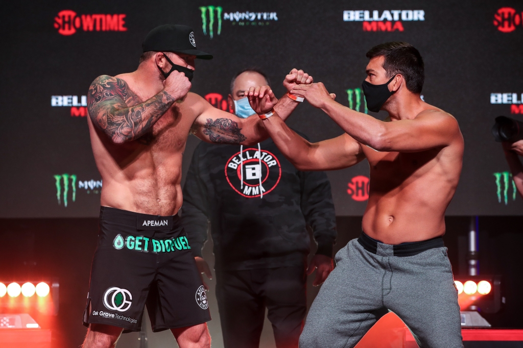Ryan Bader and Lyoto Machida face off on a stage while both wearing facemasks.
