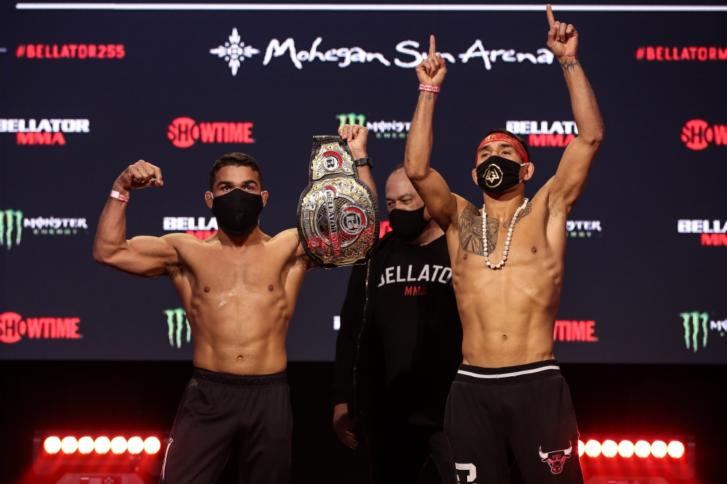 Patricio Pitbull and Emmanuel Sanchez both raise their arms while side by side at the Bellator 255 ceremonial weigh-ins.