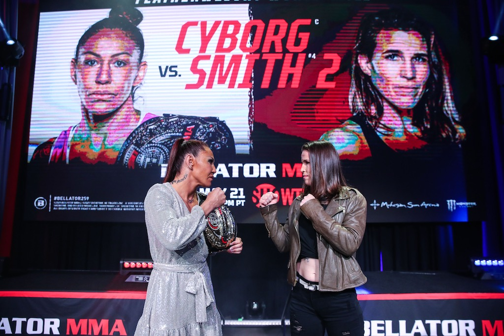 Cris Cyborg and Leslie Smith face off on the Bellator stage with a graphic displaying their names in the background.