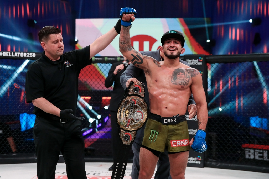Sergio Pettis gets a Bellator belt wrapped around his waist while a referee raises his right arm.