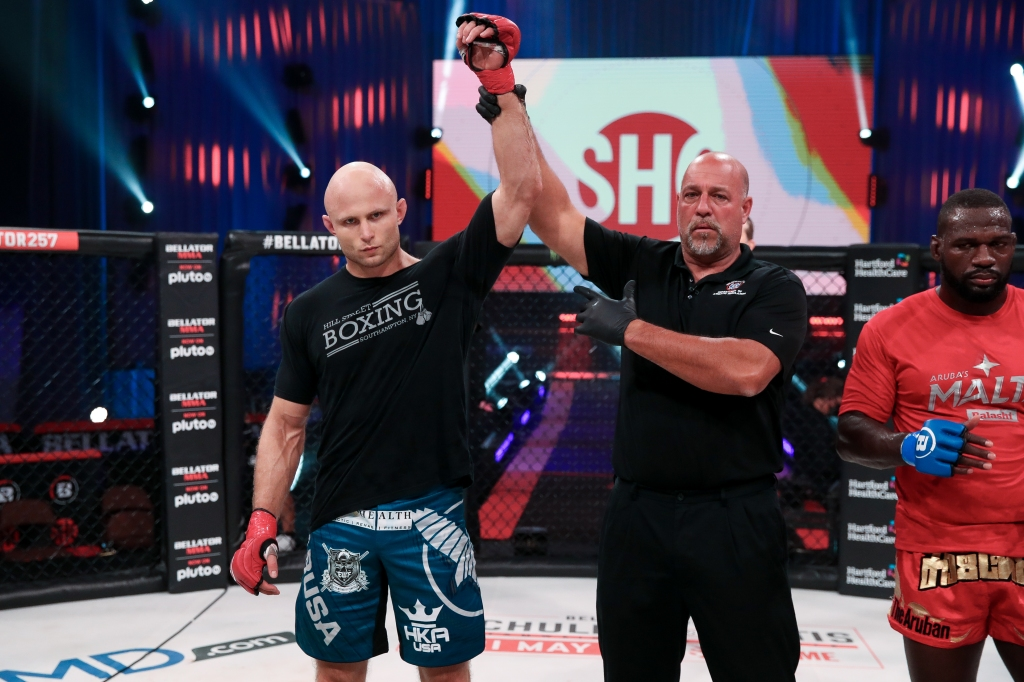 Julius Anglickas gets his arm raised by a referee in the Bellator cage.