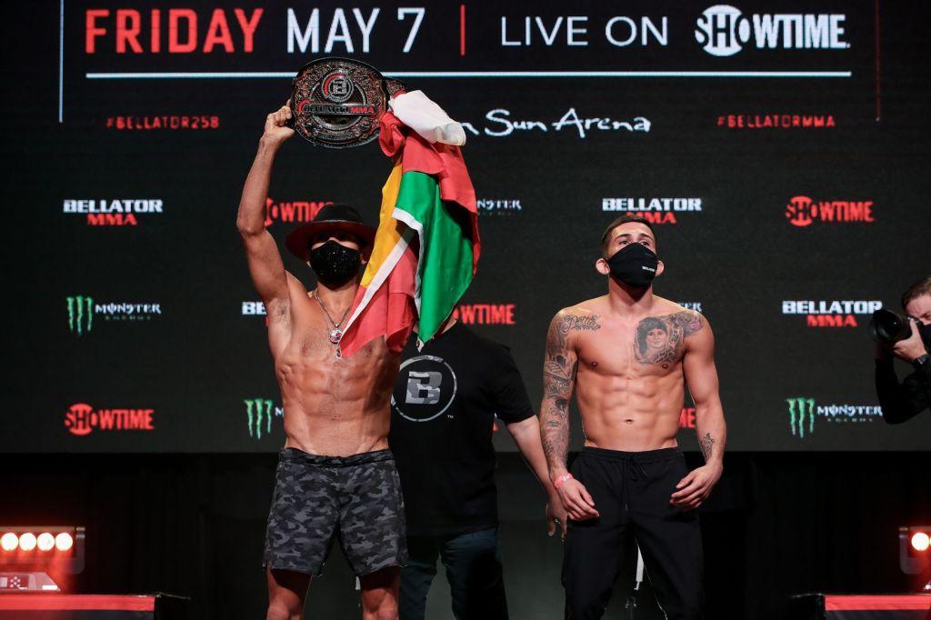 Juan Archuleta lifts his Bellator Bantamweight Championship up in the air while posing beside Sergio Pettis.
