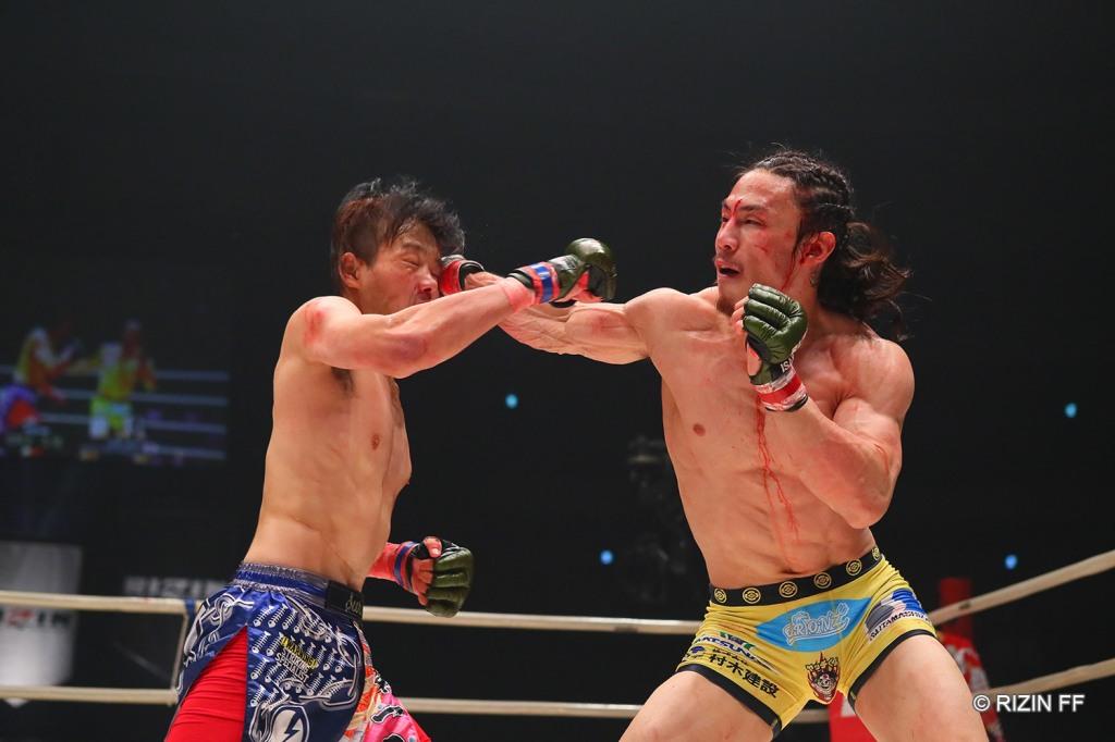 Yusuke Yachi lands a right hook to the head of Juri Ohara.