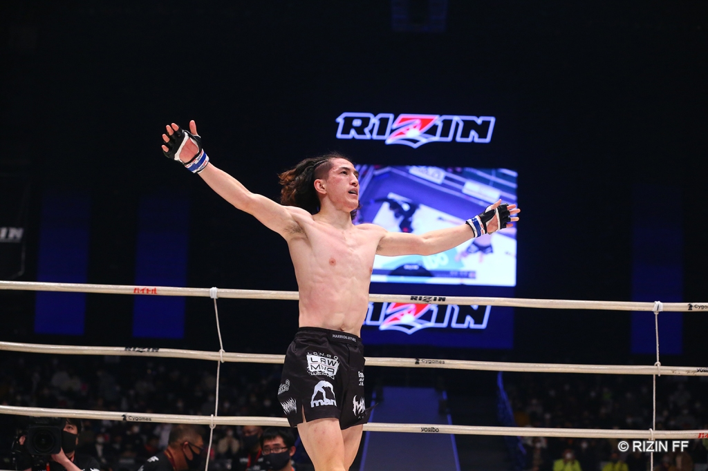 Naoki Inoue walks across the RIZIN ring with his arms up in the air.
