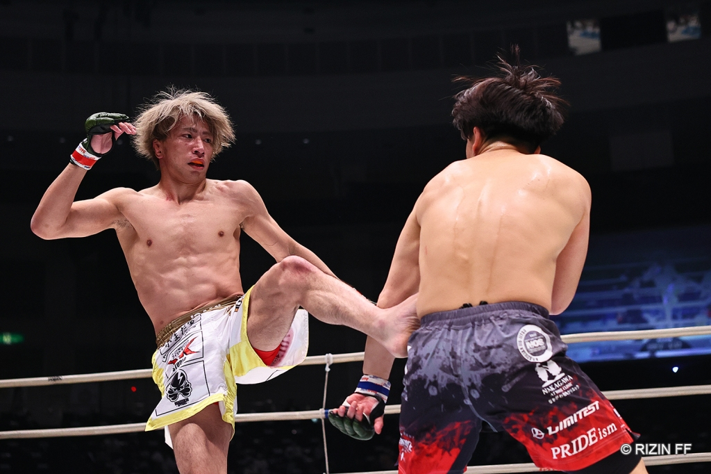 Shooto Watanabe throws a leg kick at Takumi Tamaru.