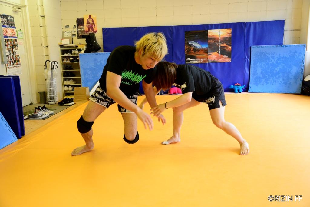Hikaru Aono shoots for a single leg takedown on Shooto Watanabe on an open grappling mat.