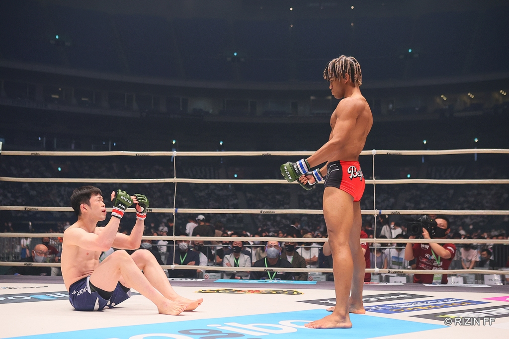 Satoshi Yamasu pleads while sitting in the RIZIN ring for BeyNoah to go to the ground for the fight. BeyNoah stands with his arms at his sides refusing to go down.