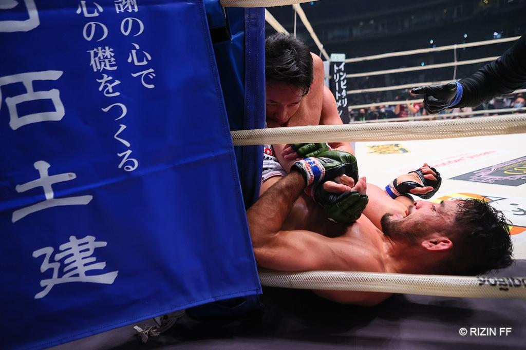 Kleber Koike applies a triangle choke to Mikuru Asakura in the corner of a RIZIN ring.