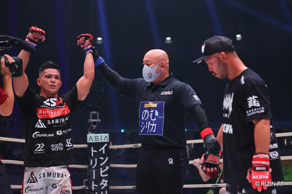 The referee raises the arm of Alan Yamaniha while Kazuma Kuramoto stands on his other side.