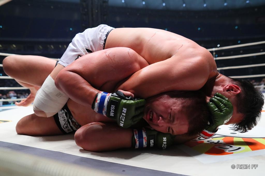 Shoma Shibisai applies a rear naked choke to Tsuyoshi Sudario.