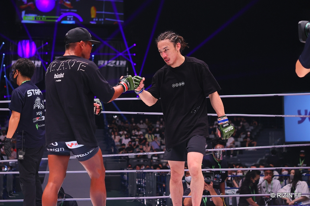 Yusuke Yachi bumps fists with Koji Takeda after their MMA fight.
