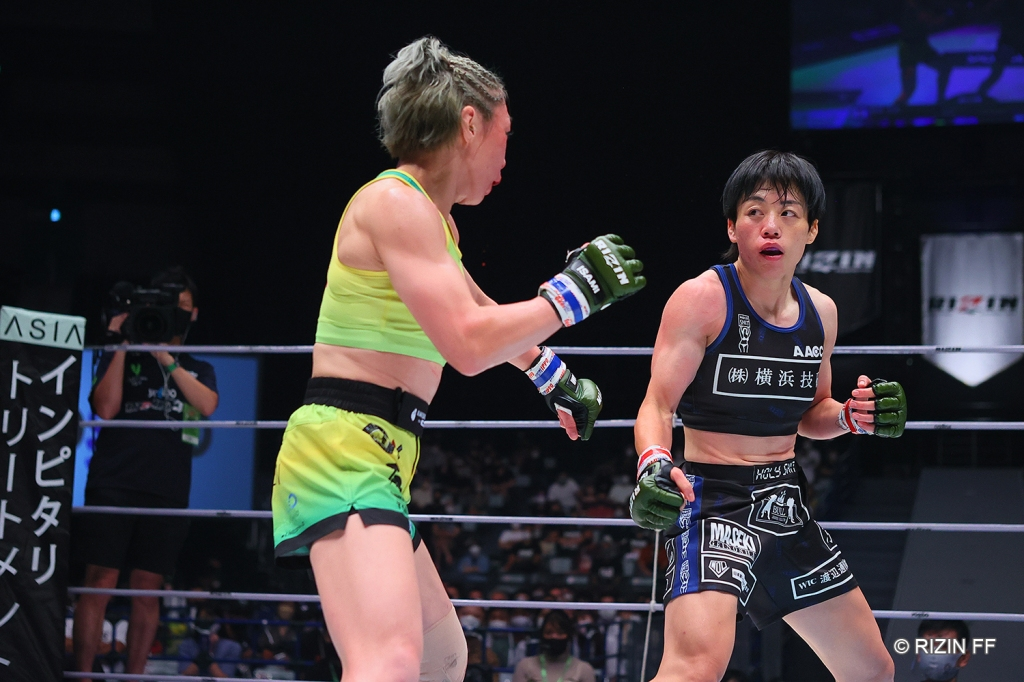 Emi Fujino and Ayaka Hamasaki standing in fighting poses in the RIZIN ring.