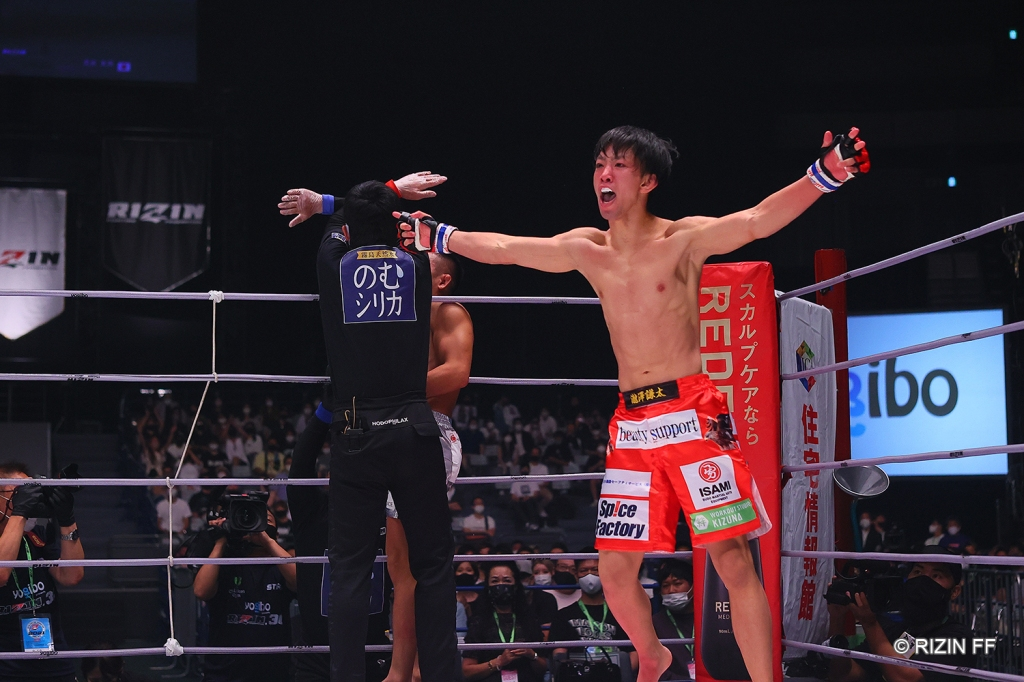 Kenta Takizawa throws his arms up in celebration as a referee waves off his fight.