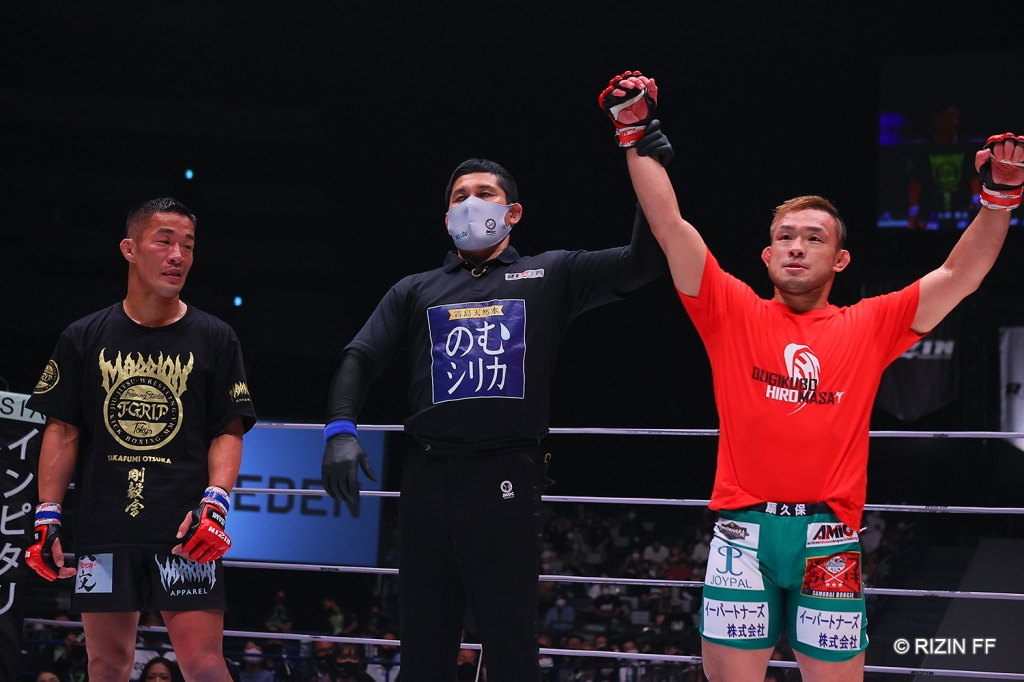 Hiromasa Ougikubo gets his arm raised by a referee during a decision announcement. On the other side of the referee, Takafumi Otsuka stands without his arm raised in victory.